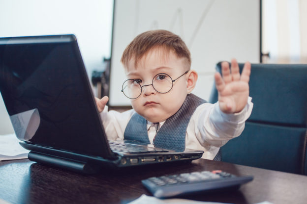 "Toddler boy in office at laptop holding his hand up as if saying ""stop"""
